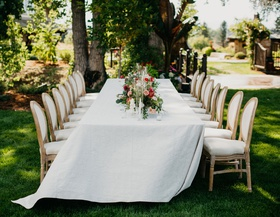wedding reception garden setting white linen french upholstered chairs low garden centerpiece flower