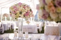 Tall centerpiece on clear glass vase with white rose, pink rose, hydrangea, and succulent details
