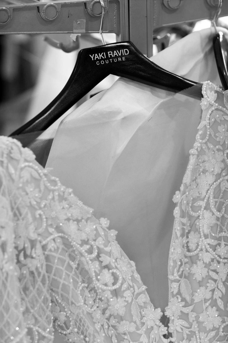 black and white up close shot of yaki ravid couture wedding dress on hanger