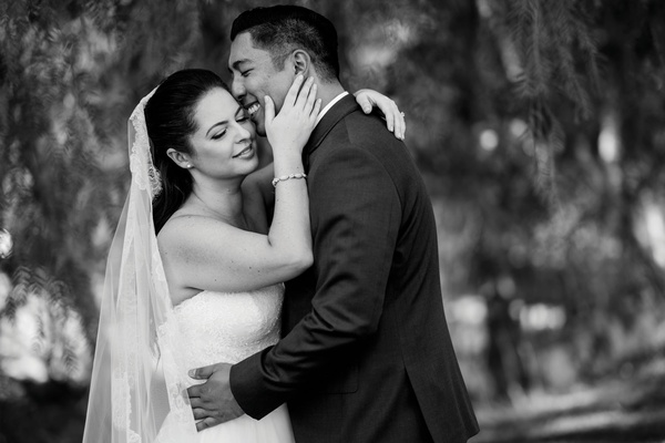 black and white photo of bride and groom with arms around each other