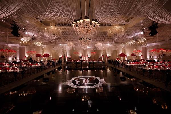 wedding reception ballroom black dance floor white monogram chandelier red rose centerpieces