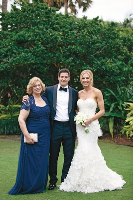 bride in strapless mermaid marchesa gown with sweetheart neckline, mother of the groom in blue