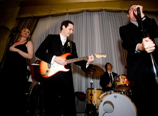 Wedding band performing on stage with groom