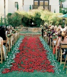 Outdoor ceremony aisle with glass disks and rose petals