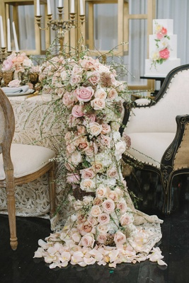 a table with a champagne and gold concept with cascading floral table runner pink flowers greenery