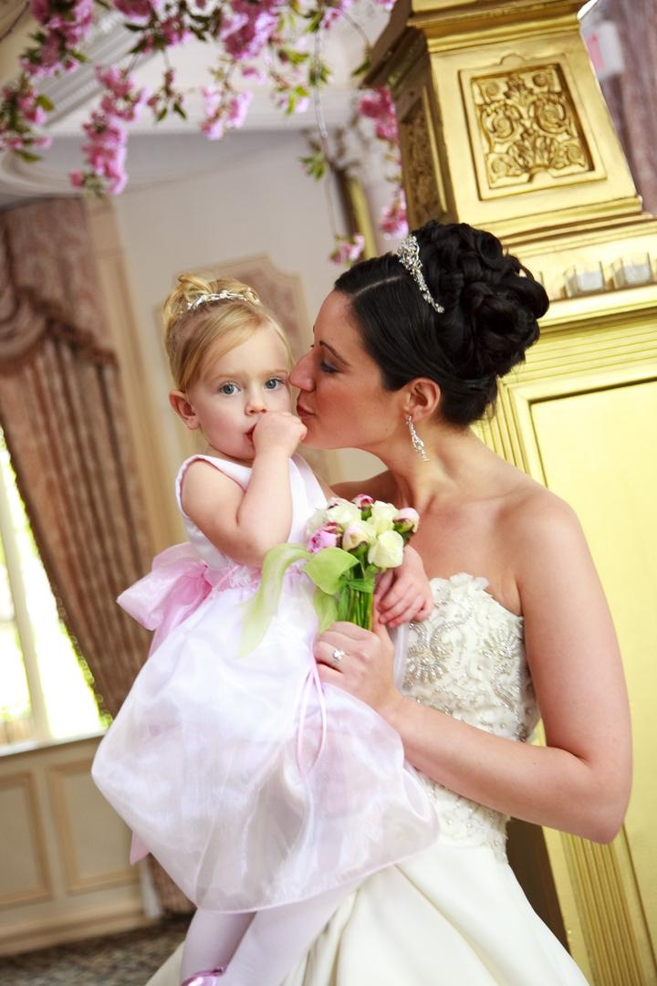 Bride in a Monique Lhuillier gown carries a flower girl in a pink sleeveless dress and tiara