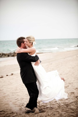 Groom lifts and spins bride on beach