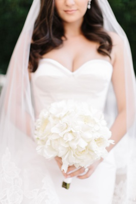Bride in strapless wedding dress with sweetheart neckline white flowers bouquet veil long brown hair