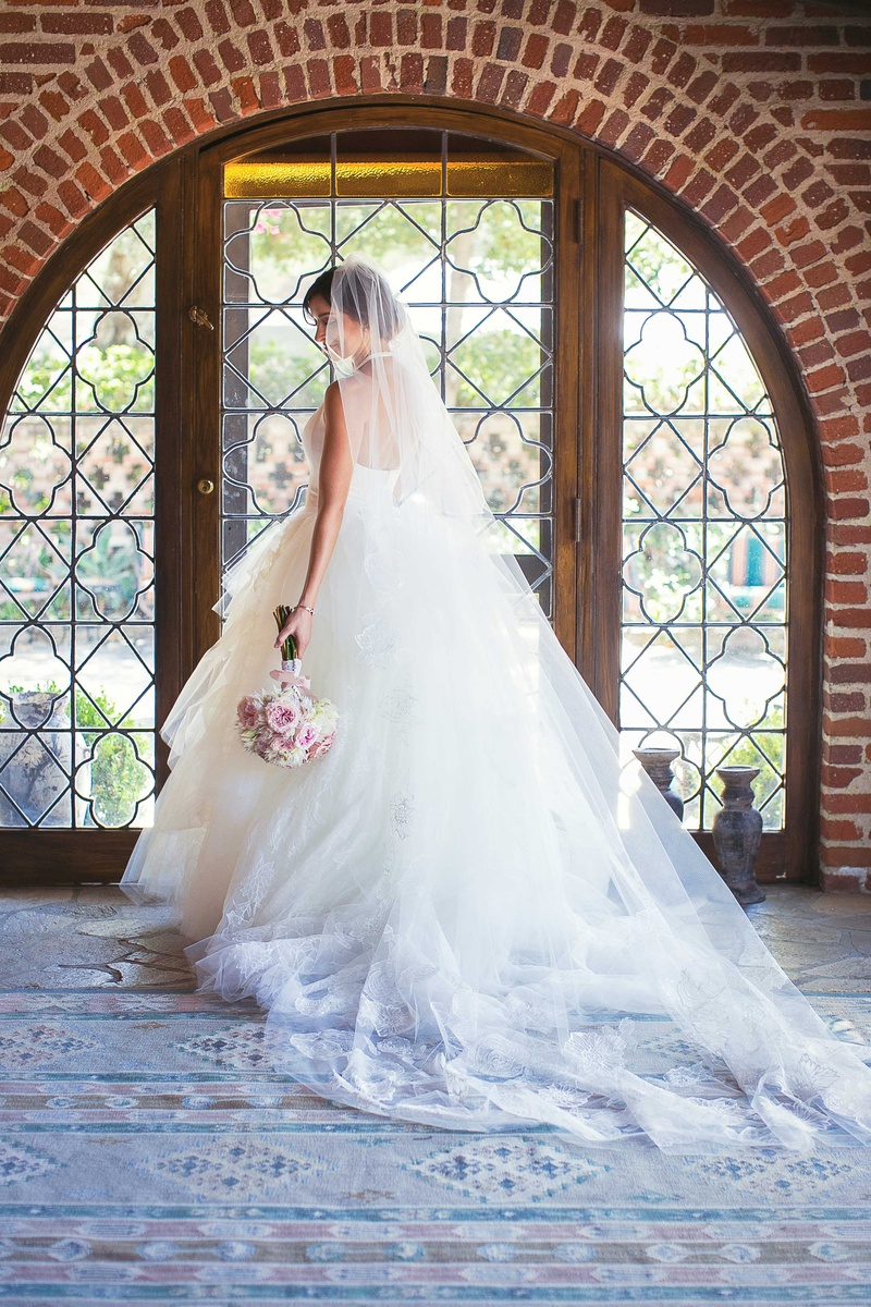 bride in white tulle ball gown with plunging halter neckline posing to show off back of dress veil