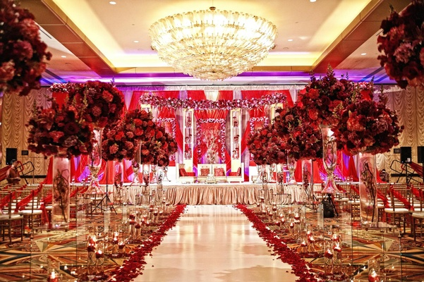 Indian wedding ceremony with red floral arrangements lining the aisle