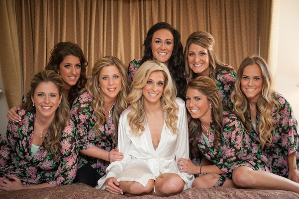 Bride in white robe with bridesmaids in dark robes with pink floral pattern, Dottie Palmer