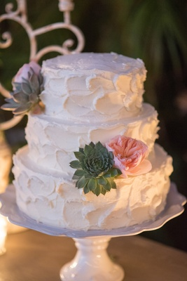 White wedding cake with textured buttercream frosting, pink garden roses, succulents