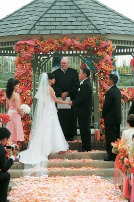Outdoor wedding ceremony in a gazebo decorated with orange and pink flowers