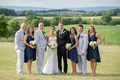 Bride in a Berta Bridal gown and groom in a navy blue Ralph Lauren tuxedo with bridal attendants