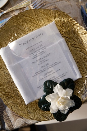 Wedding reception place setting with a gold textured charger and white gardenia