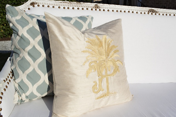 Bride and groom's wedding crest is embroidered in gold on a luxury throw pillow