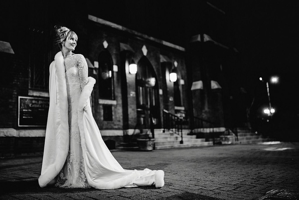 black and white photo of bride in monique lhuiller gown and fur-lined cape