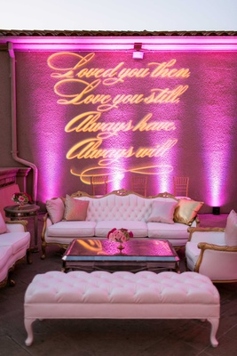 Wedding lounge with white and gold furniture, mirror coffee table, gobo lighting sign, pink uplights