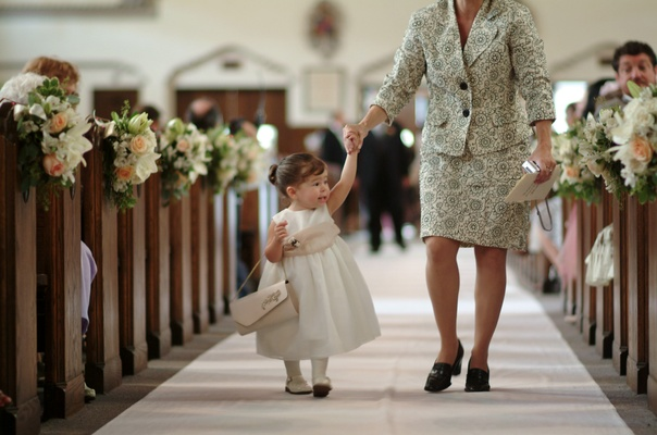 Young flower girl gets help walking down the aisle