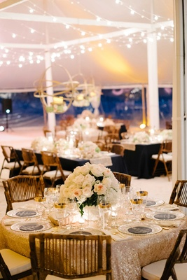 Gold sequin linen tablecloth with wood chair island wedding tent in the bahamas flower centerpiece