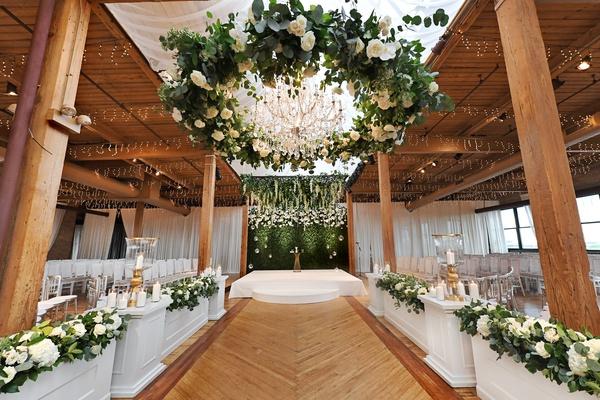 wedding ceremony wood floor aisle white boxes greenery white flowers beams wreath chandelier