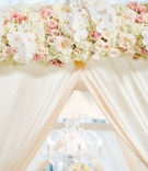 Wedding ceremony floral arch with white orchid, ivory hydrangea, and pink rose flowers and drapery