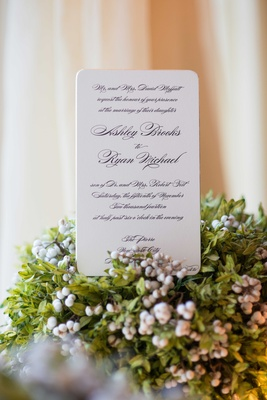 a couples white wedding invitation standing up on base of green foliage with small berries