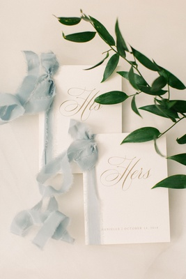 his and hers vow booklets tied together with pale blue ribbons