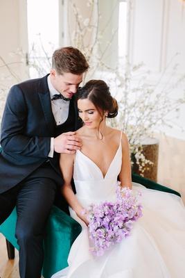 Bride in hayley paige wedding dress, bouquet of lavender sweet peas, velvet green chair