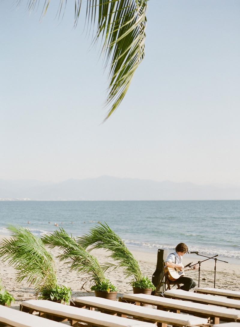 Wedding ceremony on beach palm fronds leaves plants next to white benches on sand friend playing