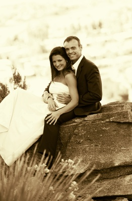 Sepia toned photo of bride and groom on rock
