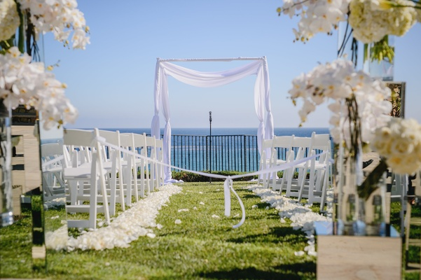 white florals, seating, and archway for a seaside ceremony.