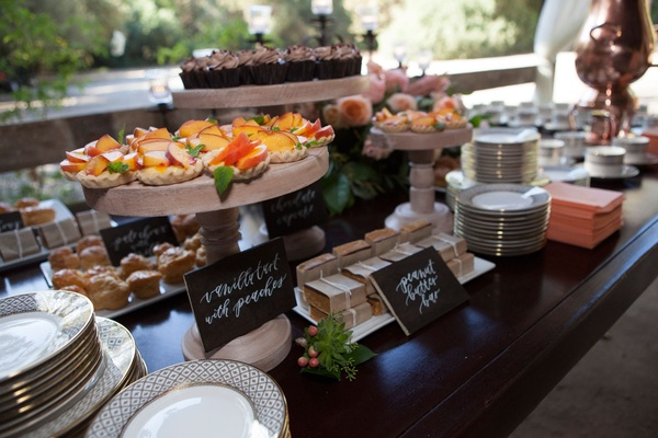 Wedding reception dessert table with wood signs and an array of cake stands and serving platters
