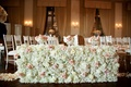 White hydrangea pink rose ivory rose flower wall along wood floor aisle ballroom wedding ceremony
