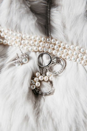 Pearl three strand bracelet, pearl earrings, and diamond rings on fur shawl