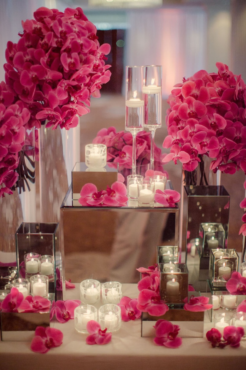 Floating candles and orchids on mirrored pedestals