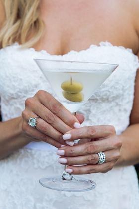 Diamond wedding band and emerald cut aquamarine ring holding martini