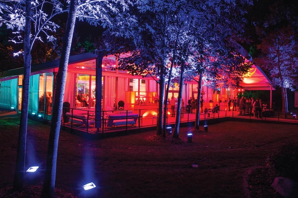 Wedding reception in a glass tent structure with covered terrace lit in red, yellow light
