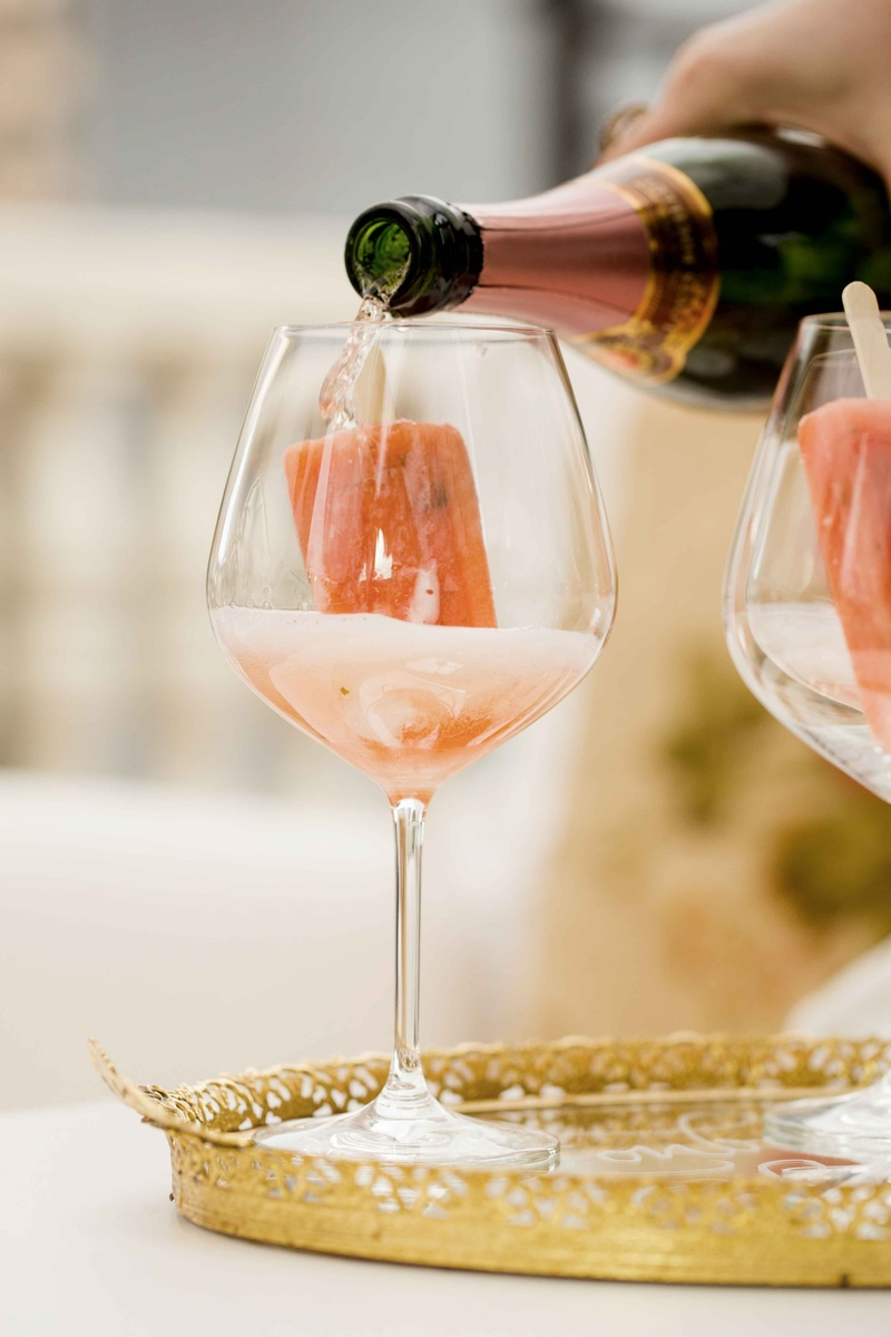 pink champagne poured over gourmet popsicles on gold tray