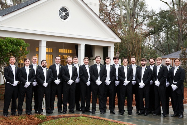 Groom and groomsmen in tuxedos white tie and gloves white vest black suit formal new year's eve