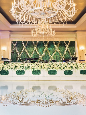 wedding reception grand chandelier over custom wedding crest dance floor hedge wall band stage