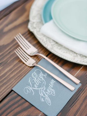 personalized blue napkins with calligraphy of couples names with silverware on a wooden table
