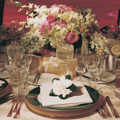 Forest green china topped with white gardenia flower