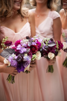 Bridesmaids holding flowers in girly colors