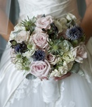 Bride holding textured flowers in white wrap