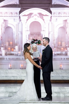 Bride in strapless wedding dress holding groom's hand during wedding female officiant vibiana
