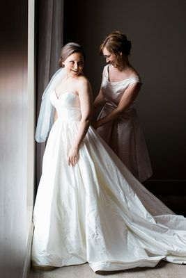 bride in justin alexander plain ball gown, mother of the bride fastens dress