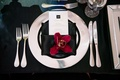 Wedding reception place setting silver charger plate black napkin burgundy orchid menu monogram
