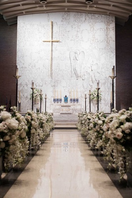 wedding ceremony at pretty church white altar flowers on church pews decorated no runner aisle