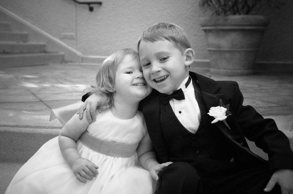 Black and white photo of young flower girl and ring bearer hugging